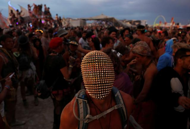 <p>A participant wears a mask as he dances as approximately 70,000 people from all over the world gathered for the annual Burning Man arts and music festival in the Black Rock Desert of Nevada, Aug. 29, 2017. (Photo: Jim Urquhart/Reuters) </p>