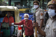 Indian policemen wearing masks stand at a traffic intersection as an elderly man pushes his cycle through a traffic jam in New Delhi, India, Monday, Sept. 21, 2020. The nation of 1.3 billion people is expected to become the coronavirus pandemic's worst-hit country within weeks, surpassing the United States. (AP Photo/Manish Swarup)