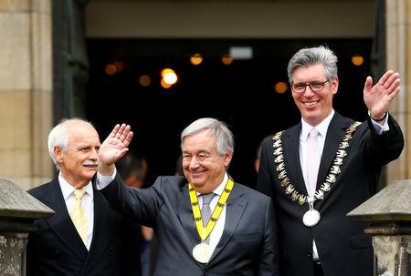 Charlemagne Prize (Karlspreis) recipient, United Nations Secretary-General Antonio Guterres, waves from the town hall balcony, flanked by former Mayor Juergen Linden and Mayor Marcel Philipp during the ceremony in Aachen, Germany May 30, 2019. REUTERS/Thilo Schmuelgen