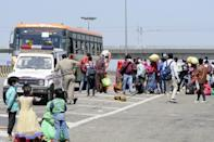 NOIDA, INDIA - MARCH 29: Stranded migrant workers rush to secure a seat on the few buses in service, on day 5 of the nationwide lockdown imposed by PM Narendra Modi to check the spread of coronavirus, at Yamuna expressway zero point, on March 29, 2020 in Noida, India. (Photo by Sunil Ghosh /Hindustan Times via Getty Images)