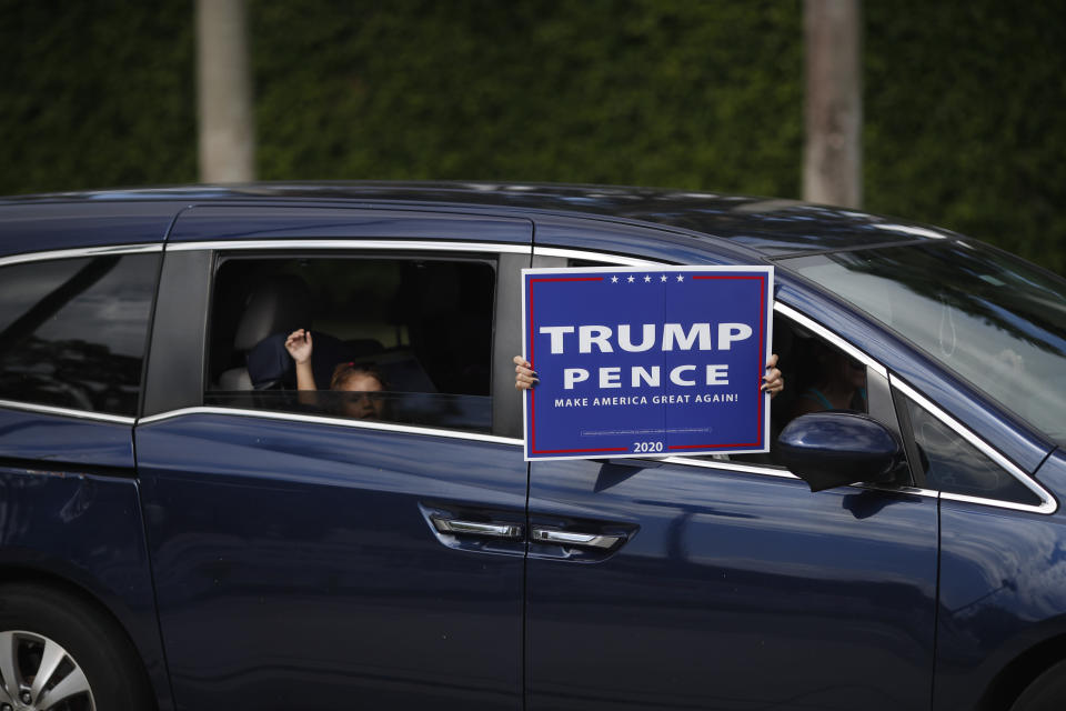 People wave a sign supporting President Donald Trump from the window of a passing car as they pass an early voting location located across the street from Trump International Golf Club in West Palm Beach, Fla., Friday, Oct. 30, 2020.(AP Photo/Rebecca Blackwell)