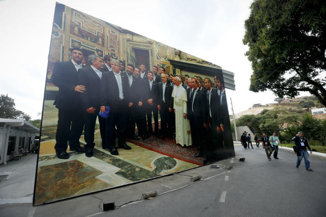 Journalists walk past a giant photo of the Argentine national soccer team with Pope Francis at the team's training ground in Vespasiano, near Belo Horizonte, Brazil, Thursday, June 12, 2014. Argentina will play in group F of the Brazil 2014 soccer World Cup. (AP Photo/Victor R. Caivano)