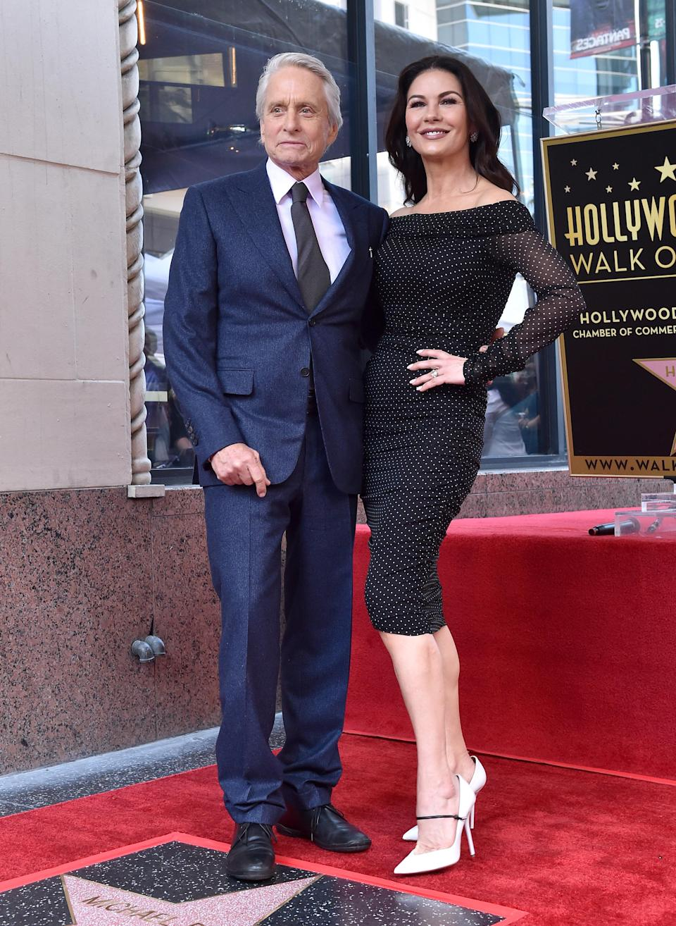 <p>Catherine, 49, picked out an off-the-shoulder, polka dot dress to wear for the unveiling of her husband's star on the Hollywood Walk of Fame. She accessorised with diamond earrings and rings, all by KALLATI. Michael, meanwhile looked dapper in a blue suit. <span><em>[Photo: Getty]</em></span> </p>
