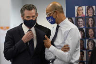 Gov. Gavin Newsom, left, speaks with Dr. Mark Ghaly, Secretary of the California Health and Human Services, at a news conference in Oakland, Calif., Monday, July 26, 2021. California will require state employees and all health care workers to show proof of COVID-19 vaccination or get tested weekly. Officials are tightening restrictions in an effort to slow rising coronavirus infections in the nation's most populous state, mostly among the unvaccinated. (AP Photo/Jeff Chiu)