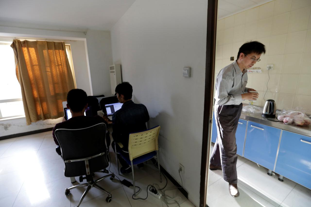 Wu Yaxiong, right, CEO of N-Wei Technology Company Ltd., fetches water at a kitchen at an apartment that he rents as an office and employees' dormitory in Beijing on April 22, 2016. (Jason Lee/Reuters)