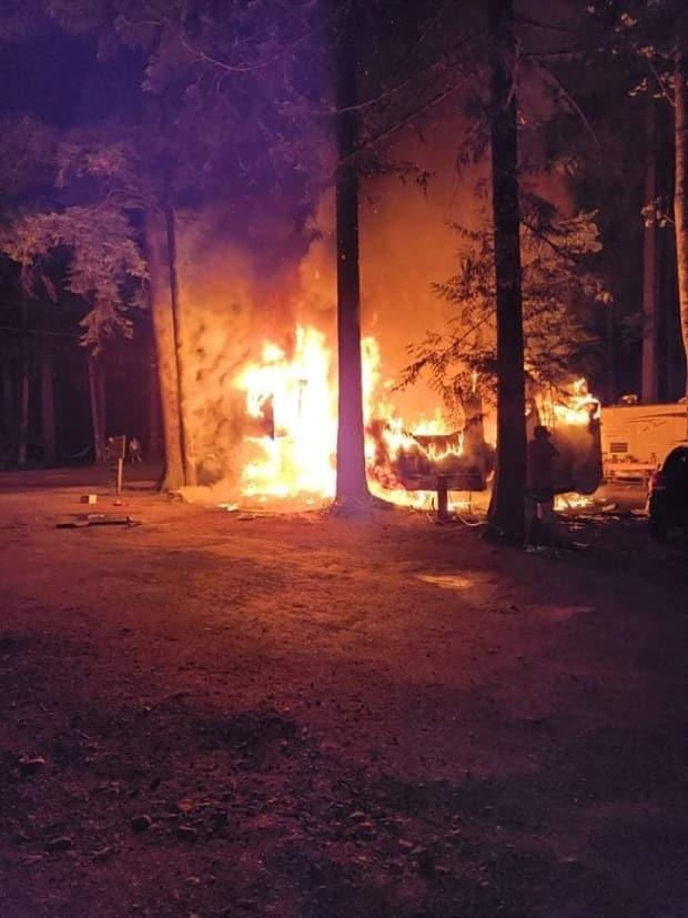 A trailer is engulfed in flames in a fire at the Sunnyside campground at Cultus Lake Provincial Park on Tuesday. (Submitted to CBC News - image credit)