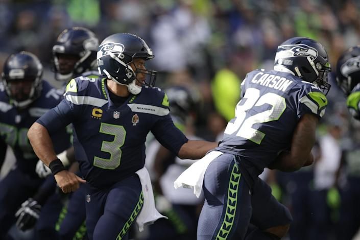 Seattle Seahawks quarterback Russell Wilson hands off to running back Chris Carson.