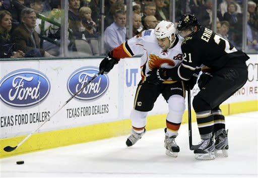 Calgary Flames defenseman Mark Giordano (5) attempts to gain control of the puck under pressure from Dallas Stars' Loui Eriksson (21) of Sweden in the first period of an NHL hockey game Monday, March 18, 2013, in Dallas. (AP Photo/Tony Gutierrez)