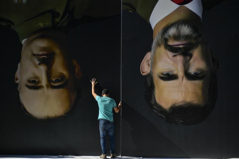 A man sets up upside down giant paintings of late Spanish dictator Francisco Franco, left, and Spanish King Felipe VI ahead of a protest by Basque pro-independence activists in support of Catalonia's independence movement following Spain's conviction of Catalan separatist leaders, in Bilbao, northern Spain, Tuesday, Oct. 15, 2019. (Photo: Alvaro Barrientos/AP)