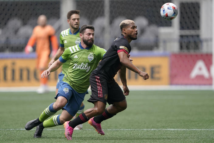 Atlanta United forward Josef Martinez, right, and Seattle Sounders midfielder Joao Paulo, center, watch the ball during the first half of an MLS soccer match, Sunday, May 23, 2021, in Seattle. (AP Photo/Ted S. Warren)