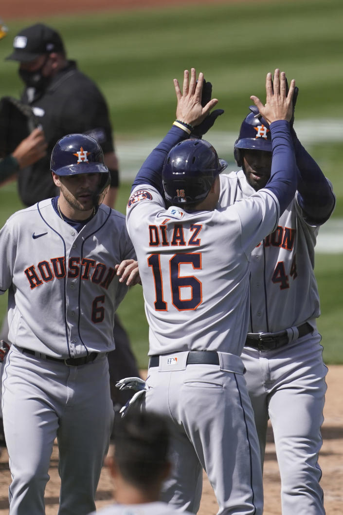 Houston Astros' Yordan Alvarez, right, celebrates after hitting a three-run home run that scored Chas McCormick, left, and Aledmys Diaz (16) during the fifth inning of the team's baseball game against the Oakland Athletics in Oakland, Calif., Saturday, April 3, 2021. (AP Photo/Jeff Chiu)