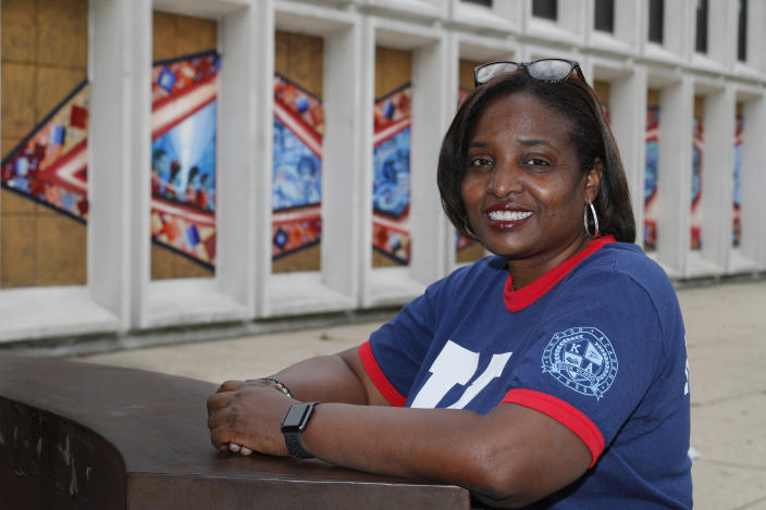 Karen Calloway, principal of Kenwood Academy in Chicago, poses Tuesday, July 28, 2020, for a portrait outside the Hyde Park neighborhood campus. School districts around the U.S. are working to remove police officers from campuses, but the school council for Kenwood Academy, a predominantly Black school near the University of Chicago, recently unanimously voted to keep its officer. (AP Photo/Charles Rex Arbogast)