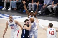 Los Angeles Clippers' Nicolas Batum (33), Terance Mann, rear, and Ivica Zubac (40) defend as Dallas Mavericks guard Luka Doncic, bottom center, moves to the basket in the second half in Game 3 of an NBA basketball first-round playoff series in Dallas, Friday, May 28, 2021. (AP Photo/Tony Gutierrez)