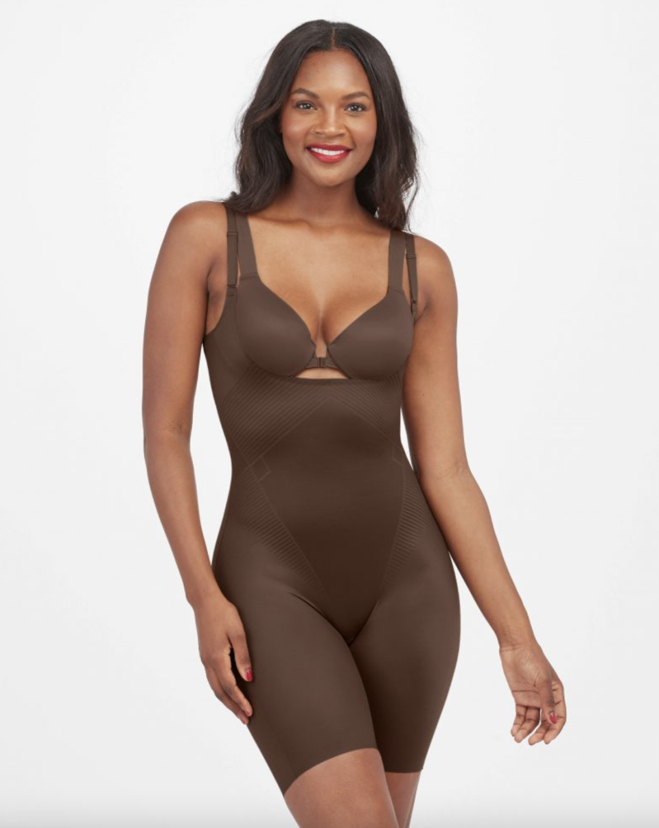 thigh-length spanx open-busy, mid-thigh bodysuit in brown on a model