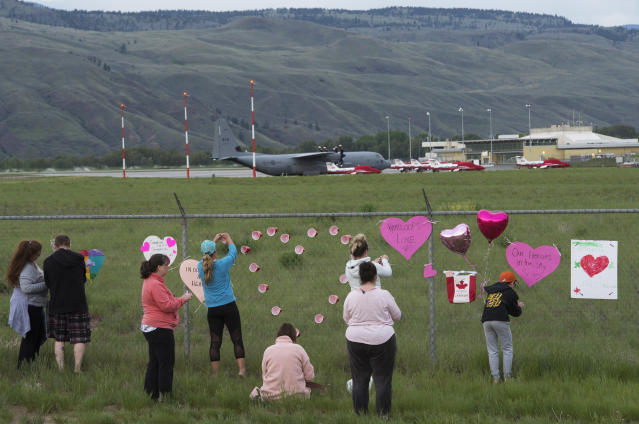 Canadian Forces Snowbirds planes are seen in the background as people place hearts and signs on the fence surrounding the airport in Kamloops, Canada, Sunday, May 17, 2020. A Canadian aerobatic jet crashed into the British Columbia neighborhood of Kamloops on Sunday during a flyover intended to boost morale during the pandemic, killing one crew member, seriously injuring another and setting a house on fire. (Jonathan Hayward/The Canadian Press via AP)