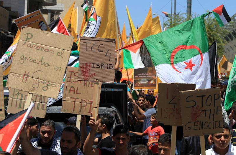 Palestinians hold placards during a demonstration against Israel's military operation in the Gaza Strip and in support of joining the ICC on August 1, 2014, in the West Bank town of Hebron