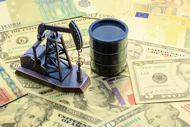 Petroleum, petrodollar and crude oil concept : Pump jack and a black barrel on US USD dollar notes, depicts the money received or earned from sales after investment in the development of oil industry.