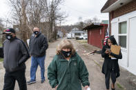 """Sue Howland, center, walks down a street to check on someone who overdosed days before with fellow members of the the Quick Response Team, from left, pastor Virgil Johnson, Sgt. Greg Moore and Larrecsa Cox, Monday, March 15, 2021, in Huntington, W.Va. Howland, the 62-year-old peer recovery coach, nearly drank herself to death. She's been sober now for 10 years. """"We're going to love them until they learn to love themselves,"""" said Howland of the people she tries to help. """"We're going to love them back to life."""" (AP Photo/David Goldman)"""