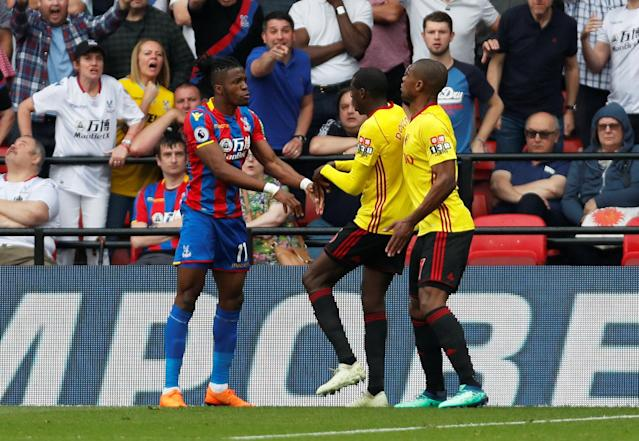 """Soccer Football - Premier League - Watford v Crystal Palace - Vicarage Road, Watford, Britain - April 21, 2018 Crystal Palace's Wilfried Zaha clashes with Watford's Abdoulaye Doucoure as Christian Kabasele intervenes Action Images via Reuters/Paul Childs EDITORIAL USE ONLY. No use with unauthorized audio, video, data, fixture lists, club/league logos or """"live"""" services. Online in-match use limited to 75 images, no video emulation. No use in betting, games or single club/league/player publications. Please contact your account representative for further details."""