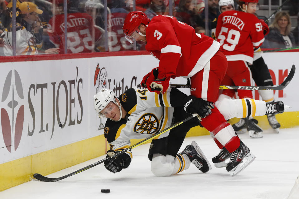 Detroit Red Wings defenseman Alex Biega (3) checks Boston Bruins right wing Chris Wagner (14) off the puck in the first period of an NHL hockey game Sunday, Feb. 9, 2020, in Detroit. (AP Photo/Paul Sancya)