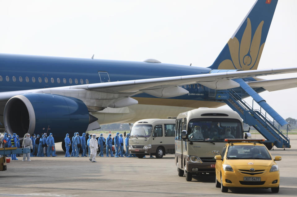 Vietnamese COVID-19 patients in protective gear arrive at the Noi Bai airport in Hanoi, Vietnam on Wednesday, July 29, 2020. The 129 patients who were working in Equatorial Guinea are brought home in a repatriation flight for treatment of the coronavirus. (Tran Huy Hung/VNA via AP)