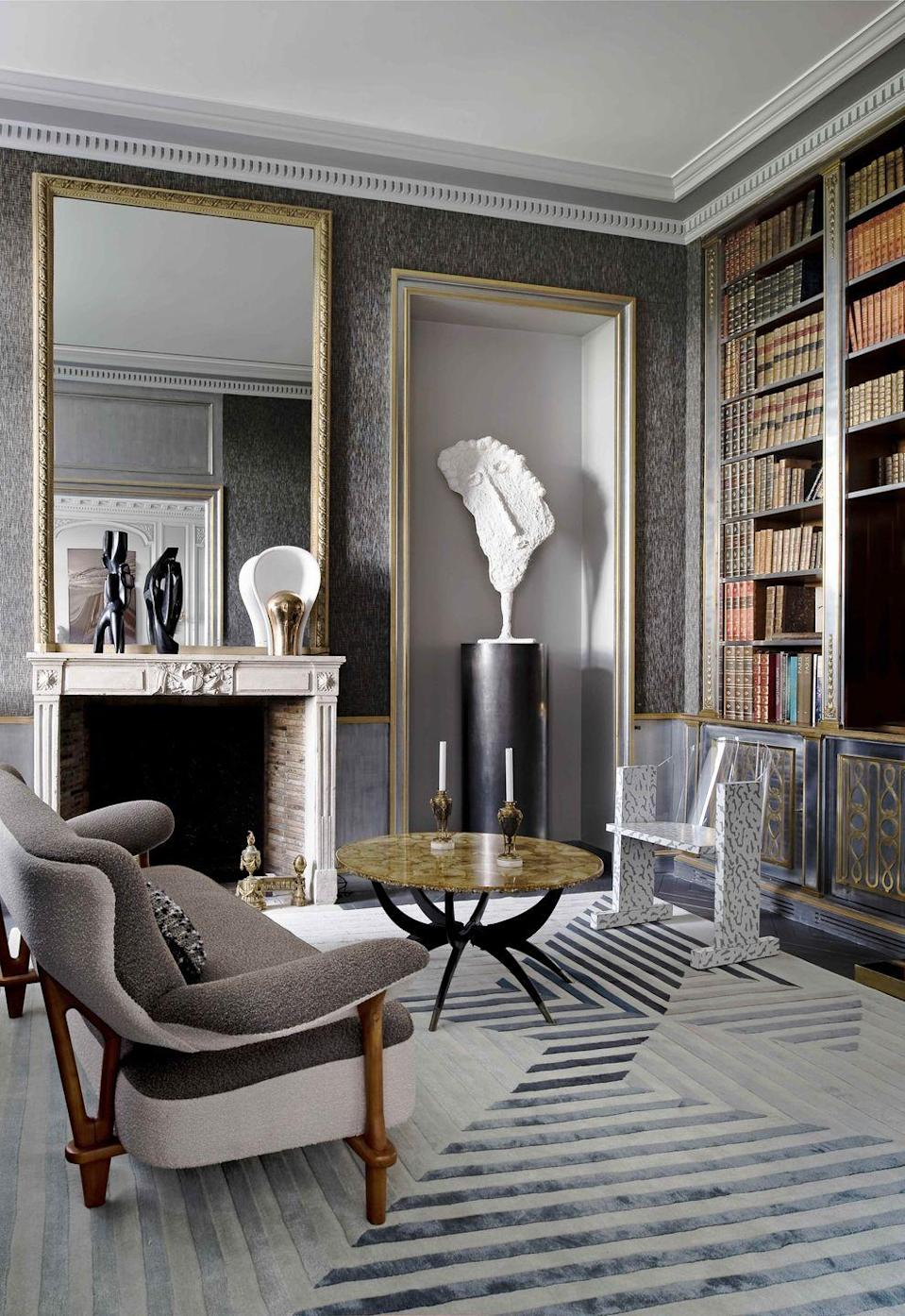 """<p>In this <a href=""""https://www.veranda.com/home-decorators/a30145127/jean-louis-deniot-paris-flat/"""" rel=""""nofollow noopener"""" target=""""_blank"""" data-ylk=""""slk:18th-century Paris flat"""" class=""""link rapid-noclick-resp"""">18th-century Paris flat</a> by designer Jean-Louis Deniot, a vintage Maison Jansen bookcase inspired the smokey tones and the layout of the library. The French designer moved the shelving originally in the dining room into its new home and repeated its metallic detailing in the wainscoting. The gold-trimmed alcove was designed specifically as a petite gallery for a figurative sculpture by Philippe Valentin.</p>"""