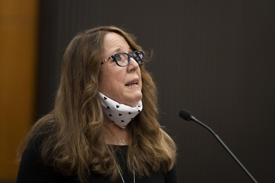 Sandy James looks up from the podium as she makes her statement with Joseph James DeAngelo, known as the Golden State Killer, in the courtroom during the first day of victim impact statements Tuesday, Aug. 18, 2020, in Sacramento, Calif. DeAngelo will be formally sentenced to life in prison Friday. (Santiago Mejia/San Francisco Chronicle via AP, Pool)