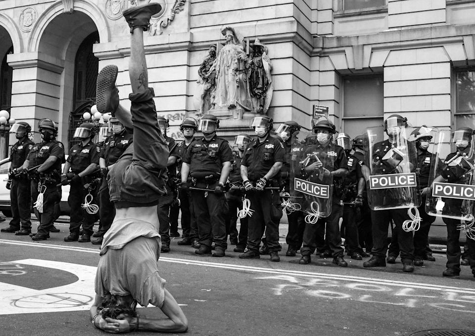 "A protester stands on his head in front of a line of NYPD near City Hall during the first attempt to take over the so-called ""Abolition Park,"" a makeshift camp in City Hall Park made up of people protesting police brutality.<span class=""copyright"">Clay Benskin</span>"