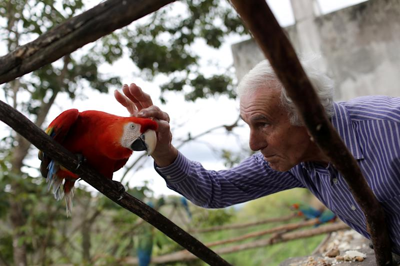 Vittorio Poggi caresses a macaw's head at his house near Caracas, Venezuela, June 18, 2019. (Photo: Manaure Quintero/Reuters)