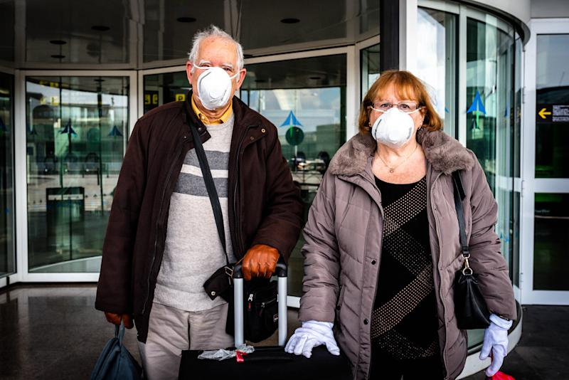 Passengers wear a face mask while walking at the international arrivals terminal in the El Prat International Airport in Barcelona on March 19, 2020. Some foreigners are still trying to come back to their countries. Many of them are in El Prat Airport trying to find a flight to come back. Flights from many companies are decreasing and some workers say that the airport its going to close in the next days. (Photo by Adria Salido Zarco/NurPhoto via Getty Images)