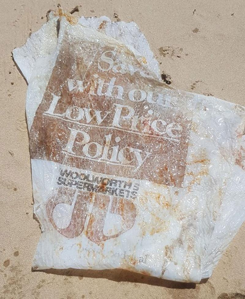 A tattered Woolworths plastic bag, estimated to be up to 30 years old, washed up on a Queensland beach.