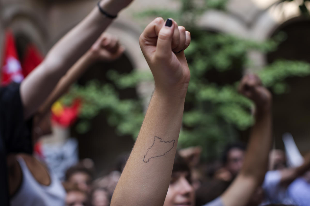 Students, on of them with the map of Catalonia tattooed on her arm, shout slogans supporting the Oct. 1 vote during a protest inside the public Barcelona University, Spain Friday, Sept. 22, 2017. Around two thousand students have gathered around and inside one of Barcelona's main universities calling to end the crackdown on a referendum on Catalonia's secession that has met a fierce opposition by Spanish central authorities. (AP Photo/Emilio Morenatti)