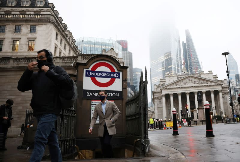 FILE PHOTO: People exit Bank station in the City of London financial district, amid the coronavirus disease (COVID-19) outbreak, in London