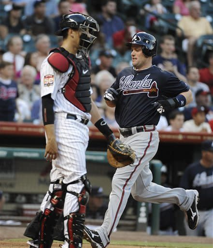 Atlanta Braves' Matt Diaz, right, crosses the plate beside Houston Astros catcher Jason Castro in the second inning of a baseball game Monday, April 9, 2012, in Houston. (AP Photo/Pat Sullivan)