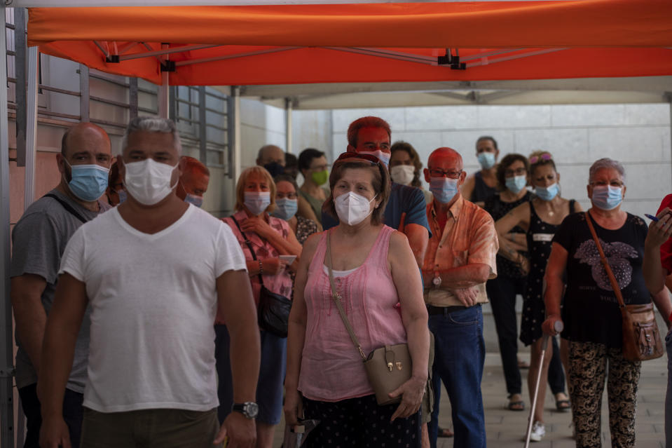 People wearing face masks queue up to be tested for COVID-19, outside a local clinic in Santa Coloma de Gramanet in Barcelona, Spain, Tuesday, Aug. 11, 2020. Spain is facing another surge in coronavirus infections not even two months after beating back the first wave. (AP Photo/Emilio Morenatti)
