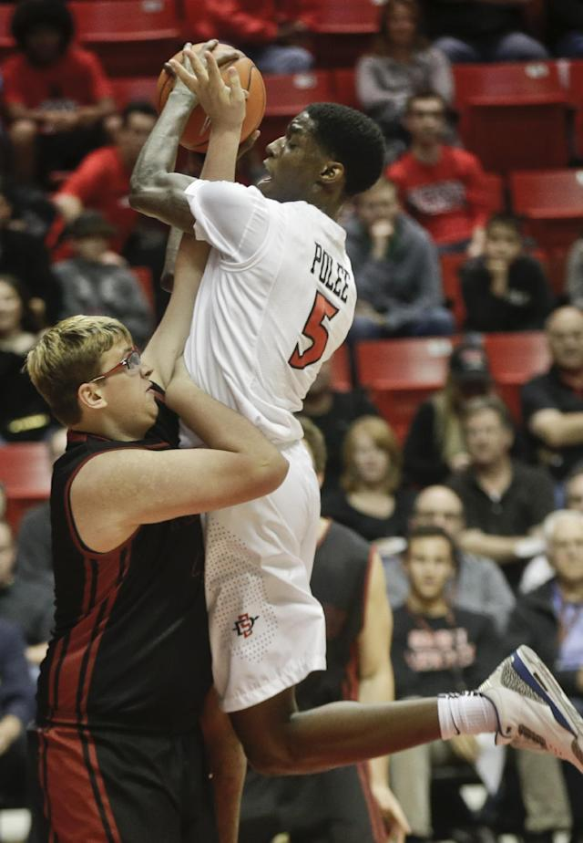 San Diego State forward Dwayne Polee, top, becomes entangled with Saint Katherine center Jimmy Roethler during the first half of an NCAA college basketball game on Friday Dec. 27, 2013 in San Diego. Roether got called for a foul. (AP Photo/Lenny Ignelzi)