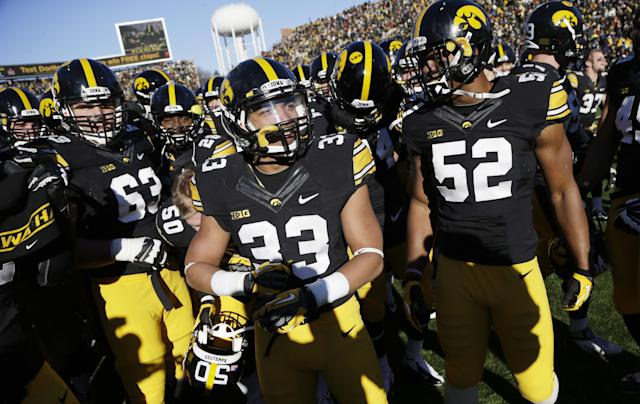 Iowa running back Jordan Canzeri, center, celebrates with teammates after their 24-21 victory over Michigan in an NCAA college football game, Saturday, Nov. 23, 2013, in Iowa City, Iowa. (AP Photo/Charlie Neibergall)