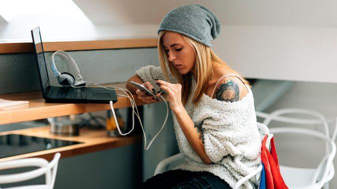 Young tattooed female developer working in her start-up office.