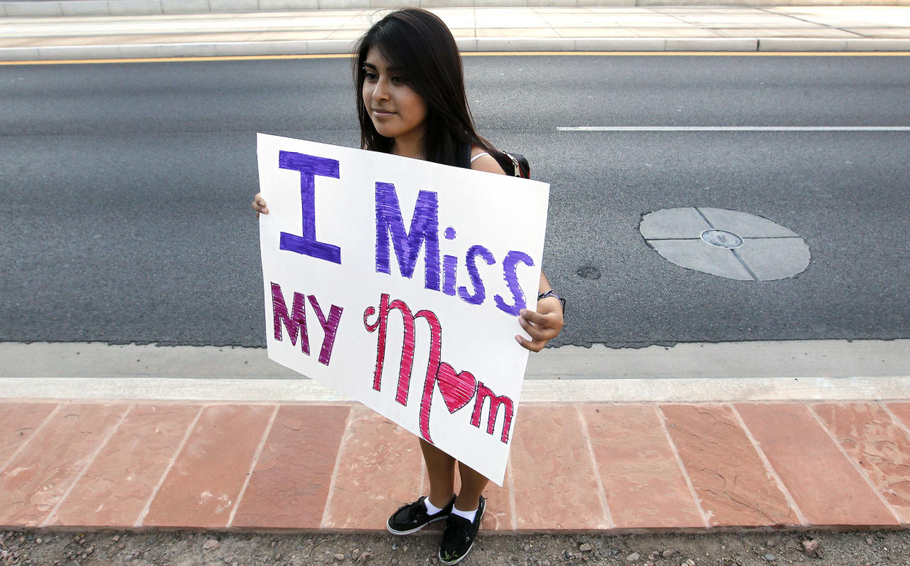 """Cynthia Diaz, 17, quietly holds up a sign telling her story of her Mom's deportation last year, as she joins dozens who rally in front of U.S. Immigration and Customs Enforcement building, a day after a portion of Arizona's immigration law took effect, Wednesday, Sept. 19, 2012, in Phoenix. Civil rights activists contend will lead to systematic racial profiling, as the protesters chanted """"No papers, no fear."""" (AP Photo/Ross D. Franklin)"""