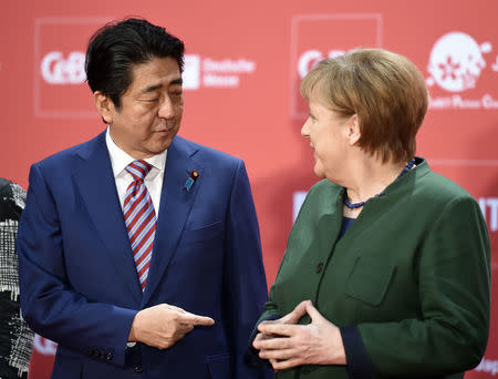 German Chancellor Angela Merkel and Japanese Prime Minister Shinzo Abe attend the opening ceremony of the CeBit computer fair, which will open its doors to the public on March 20, at the fairground in Hanover, Germany, March 19, 2017.    REUTERS/Fabian Bimmer