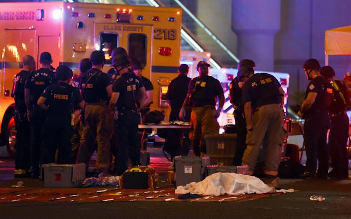 <p>A body lies under a sheet as fire and rescue personnel gather at the intersection of Las Vegas Boulevard and Tropicana Ave. after a mass shooting at a country music festival nearby on Oct. 1, 2017 in Las Vegas, Nevada. (Photo: Ethan Miller/Getty Images) </p>