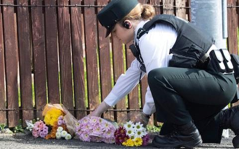 A police officer lays down flowers at the site of Lyra McKee's murder - Credit: JOE BOLAND/NORTH WEST NEWSPIX/EPA-EFE/REX