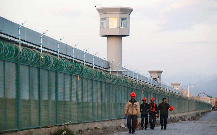 Workers walk by the perimeter fence of what is officially known as a vocational skills education centre in Dabancheng in Xinjiang -  Thomas Peter/Reuters