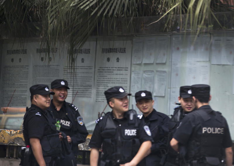UPDATING THE CAPTION WHEN THE TRIAL STARTED - Chinese policemen huddle near the Chengdu Intermediate People's Court in Chengdu in southwest China's Sichuan province Monday, Sept. 17, 2012. The trial of Wang Lijun, an ex-police chief at the center of China's worst political scandal in decades, started unexpectedly at the court Monday, a day earlier than the court had announced. At the height of his career, Wang led a police crackdown on the violent underworld in a sprawling metropolis, arresting hundreds of gangsters and government officials, some of whom were sentenced and executed in a matter of months. Now the former police chief is in the hands of the opaque Chinese justice he once brandished against others. (AP Photo/Andy Wong)