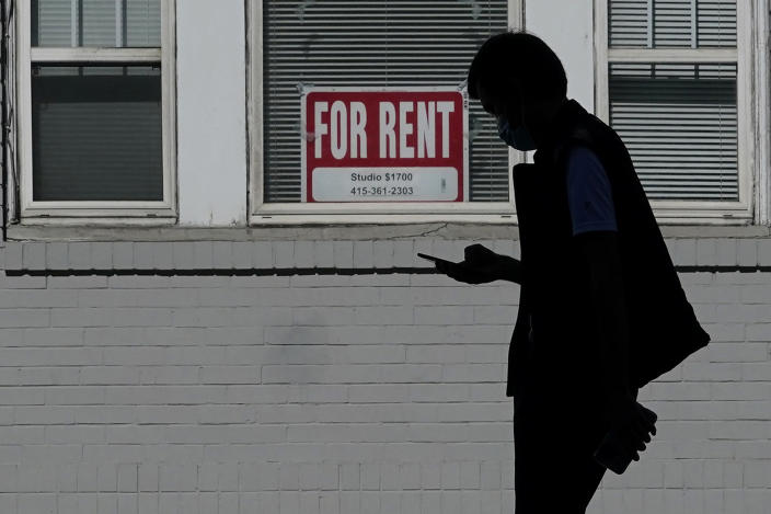 FILE - In this Oct. 20, 2020 file photo, a man walks in front of a For Rent sign in a window of a residential property in San Francisco. The Biden administration on Friday, May 7, 2021, announced the allocation of $21.6 billion to provide emergency rental assistance to help prevent evictions of people who lost jobs during the pandemic. (AP Photo/Jeff Chiu, File)