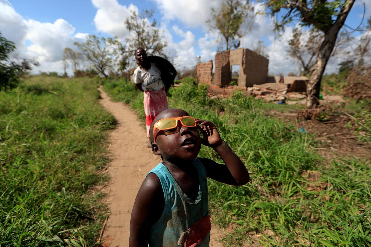 Ester Thoma walks past her damaged house as a boy plays with his glasses. (Photo: Zohra Bensemra/Reuters)