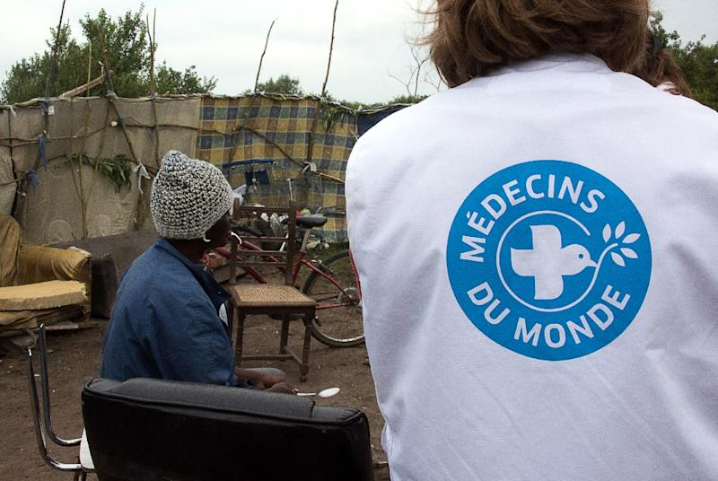 """File picture shows a volunteer from the humanitarian NGO Medecins du Monde (Doctors of the World) standing next to a migrant, in the site dubbed """"new jungle"""" around the northern French port of Calais (AFP Photo/Denis Charlet)"""