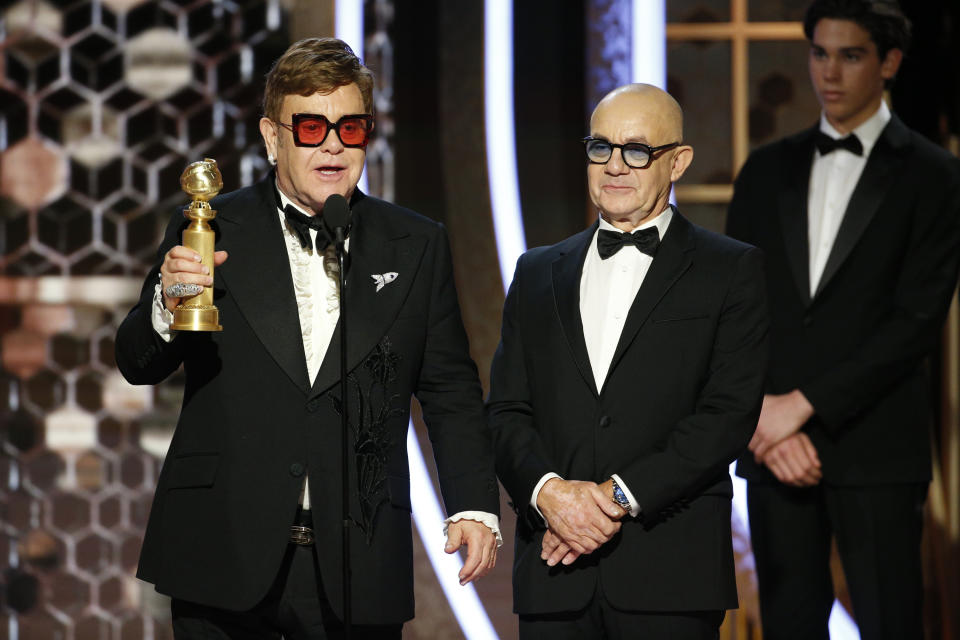 """BEVERLY HILLS, CALIFORNIA - JANUARY 05: In this handout photo provided by NBCUniversal Media, LLC,  Sir Elton John and Bernie Taupin accept the award for BEST ORIGINAL SONG - MOTION PICTURE for """"I'm Gonna Love Me Again"""" in """"Rocketman"""" onstage during the 77th Annual Golden Globe Awards at The Beverly Hilton Hotel on January 5, 2020 in Beverly Hills, California. (Photo by Paul Drinkwater/NBCUniversal Media, LLC via Getty Images)"""