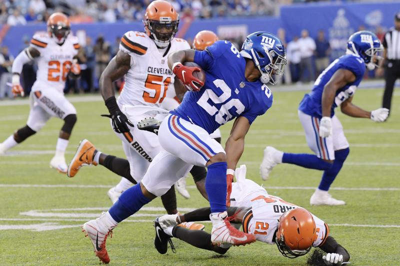 New York Giants running back Saquon Barkley (26) rushes past Cleveland Browns' Denzel Ward (21) during the first half of a preseason NFL football game Thursday, Aug. 9, 2018, in East Rutherford, N.J. (AP Photo/Bill Kostroun)