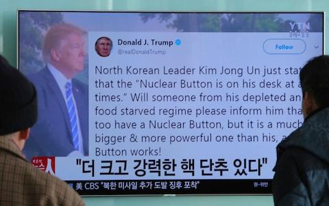 People watch a TV news program showing the Twitter post of U.S. President Donald Trump while reporting North Korea's nuclear issue, at Seoul Railway Station in Seoul, South Korea - Credit: AP Photo/Ahn Young-joon